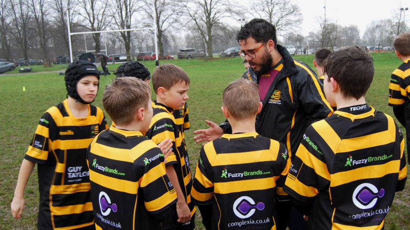 Sponsored rugby team being coached.